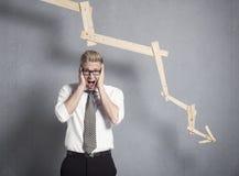 Homem de negócios devastado que shouting na frente do gráfico que aponta para baixo. Imagem de Stock