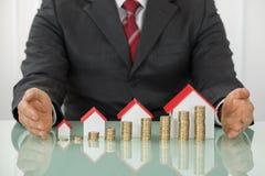 Homem de negócios With Different Houses e pilhas de moedas foto de stock