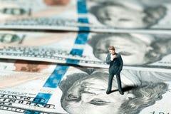 Homem de negócios diminuto da estatueta com 100 dólares de cédula no fundo Fotografia de Stock Royalty Free