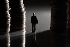 Homem de negócios diminuto que anda entre a pilha da moeda fotos de stock royalty free