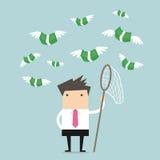 Homem de negócios do conceito que tenta travar a mosca do dinheiro Fotografia de Stock Royalty Free