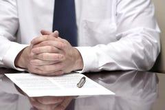 Homem de negócios do homem de negócio na mesa com o contrato que faz a mão Gestu Imagens de Stock