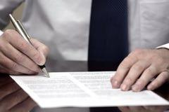 Homem de negócios do homem de negócio na mesa com o contrato que faz a mão Gestu Imagem de Stock Royalty Free