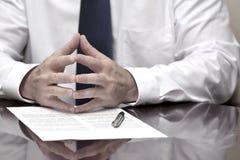 Homem de negócios do homem de negócio na mesa com o contrato que faz a mão Gestu Imagem de Stock