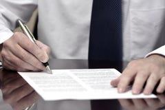 Homem de negócios do homem de negócio na mesa com o contrato que faz a mão Gestu Foto de Stock Royalty Free