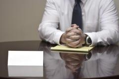 Homem de negócios do homem de negócio na mesa com papéis e cartão que faz Han Imagem de Stock Royalty Free