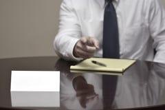 Homem de negócios do homem de negócio na mesa com papéis e cartão que faz Han Foto de Stock