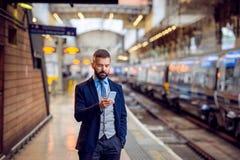 Homem de negócios do moderno com o smartphone, esperando no platfo do trem Fotos de Stock