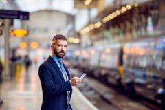 Homem de negócios do moderno com o smartphone, esperando, plataforma do trem Fotografia de Stock Royalty Free