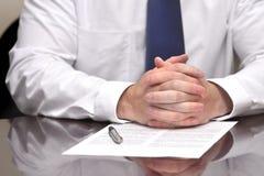 Homem de negócios do homem de negócio na mesa com o contrato que faz a mão Gestu Fotografia de Stock