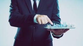 Homem de negócios do sucesso que usa a mostra digital da tabuleta a skyline da cidade imagem de stock royalty free