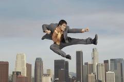 Homem de negócios Doing Martial Arts contra a arquitetura da cidade imagem de stock
