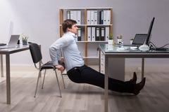 Homem de negócios Doing Triceps Dips no escritório foto de stock