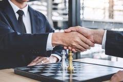 Homem de negócios dois que agita as mãos após a extremidade que joga o plano de alcance do jogo de xadrez para o sucesso, pensand fotografia de stock
