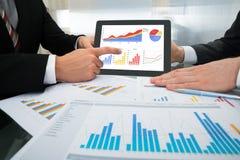 Homem de negócios dois que discute o gráfico na tabuleta digital imagens de stock royalty free
