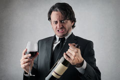 Homem de negócios duvidoso com um vidro e uma garrafa do vinho Foto de Stock Royalty Free