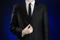 Homem de negócios e assunto do gesto: um homem em um terno preto e em uma camisa branca que corrigem um revestimento e laço em um Imagem de Stock