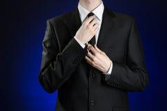 Homem de negócios e assunto do gesto: um homem em um terno preto e em uma camisa branca que corrigem um revestimento e laço em um Fotografia de Stock Royalty Free
