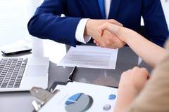 Homem de negócios e mulher de negócio que agita as mãos entre si acima do contrato assinado Fotos de Stock Royalty Free
