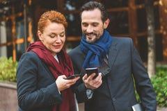 Homem de negócios e mulher de negócios alegres que usa smartphones fotos de stock royalty free
