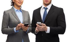 Homem de negócios e mulher de negócios com smartphones Fotografia de Stock Royalty Free