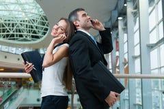 Homem de negócios e mulher de negócios de volta à parte traseira em telefones celulares Imagens de Stock
