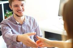 Homem de negócios e mulher de negócios que agitam as mãos no escritório Fotografia de Stock Royalty Free