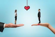 Homem de negócios e mulher de negócios que estão nas mãos com coração tirado entre elas Imagem de Stock