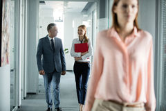 Homem de negócios e mulher de negócios que falam ao andar no corredor do escritório com o colega fêmea no primeiro plano imagem de stock royalty free