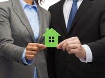 Homem de negócios e mulher de negócios que guardam a casa verde Imagem de Stock