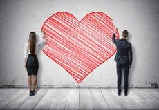 Homem de negócios e mulher de negócios que tiram o coração vermelho grande no muro de cimento Fotografia de Stock Royalty Free