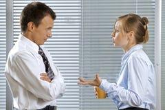 Homem de negócios e mulher na conversação no escritório fotografia de stock