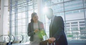 Homem de negócios e mulher de negócios que agitam as mãos um com o otro na entrada no escritório 4k video estoque