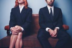 Homem de negócios e mulher que esperam no sofá na entrada Fotografia de Stock Royalty Free