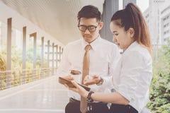 Homem de negócios e mulher que usa a tabuleta do trabalho Reuniões as atividades comerciais na promoção Crie junto um mutuamente  imagem de stock royalty free