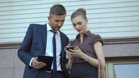 Homem de negócios e mulher que usa a tabuleta e o telefone celular digitais perto do escritório 4K vídeos de arquivo
