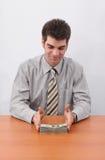 Homem de negócios e pilha de dinheiro Fotografia de Stock Royalty Free