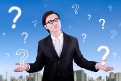Homem de negócios e ponto de interrogação pensativos Fotografia de Stock