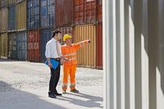 Homem de negócios e trabalhador com recipientes de carga Foto de Stock