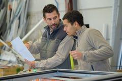 Homem de negócios e trabalhador que verificam o inventário no grande armazém foto de stock royalty free