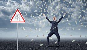 Homem de negócios ectático que está sob muitas notas de dólar que caem do céu com um ` do dinheiro do ` do sinal de aviso do tráf Fotografia de Stock Royalty Free