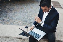 Homem de negócios elegante atrativo que usa o caderno contemporâneo e o smartphone que sentam-se fora Fundo borrado horizontal fotos de stock royalty free