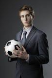 Homem de negócios elegante que guardara uma bola de futebol imagens de stock