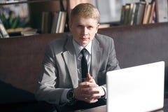 Homem de negócios elegante que senta-se na mesa com portátil Imagem de Stock Royalty Free