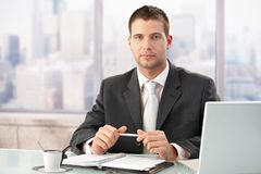 Homem de negócios elegante que senta-se no escritório brilhante Imagens de Stock