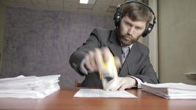 Homem de negócios em originais entrantes de assinatura dos fones de ouvido e de carimbo funy video estoque