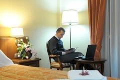 Homem de negócios em um quarto de hotel Fotografia de Stock Royalty Free