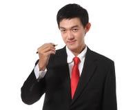 Homem de negócios em um terno com uma cor do laço do ouro que guarda uma pena e um wr Foto de Stock