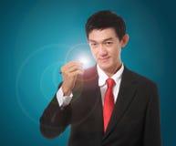 Homem de negócios em um terno com uma cor vermelha do laço que guarda uma pena e um wri Foto de Stock