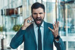 Homem de negócios em um terno fromal em um close-up furioso do telefonema do centro de negócios imagem de stock royalty free